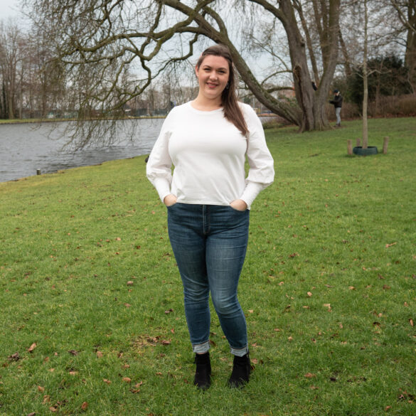 Bri stands on the park lawn in her new white long poofy sleeved tee shirt. It is paired with blue skinny jeans and black boots.  In the background is a large oak tree with limbs dipping into the water.