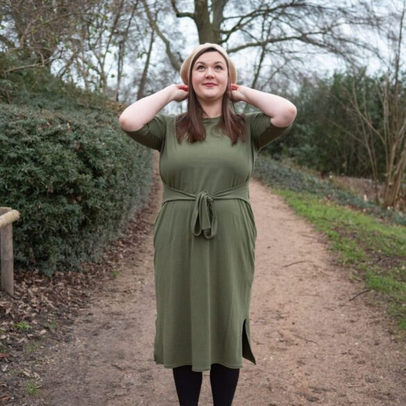 Bri stands on gravel path wearing an olive green tee shirt dress. She looks up with both hands touching her beige beret.