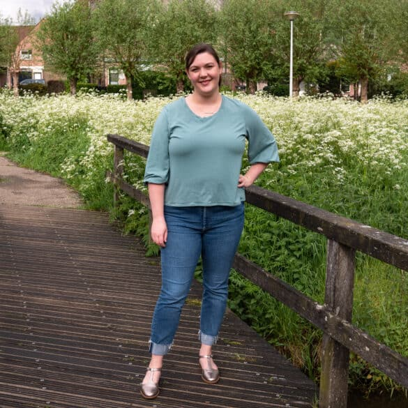Bri, a white small-fat fem, stands on a bridge with her hand on her hip. She's smiling at the camera wearing a sea-foam green tee shirt with three quarter puffed sleeves and jeans.