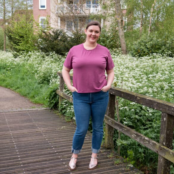 Bri, a white small fat femme, stands on a bridge surrounded by tall white flowers. She wears a purple tee shirt, blue jeans and metallic flats. She is smiling at the camera with her hands in her pockets.