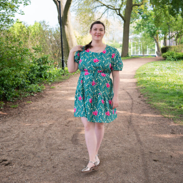 Bri stands on a park path. She touches her shoulder and looks at the camera. She's wearing a green and gold poofy sleeved dress with bright pink magnolias on it.
